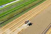 Nederland, Groningen, Carel Coenraadpolder, 05-08-2014;  graanoogst in het Oldambt. De combine maait het graan en dorst dit direct, het zgn. maaidorsen. Naast de maaidorser (een Claas Lexicon 600) een kipper voor de afvoer van het graan. <br /> De CC-polder is een zeekleipolder leggen aan de Dollard Noordoost-Groningen.<br /> Grain harvest in the Oldambt. The combine reaps the grain and threases it. Next to the combine harvester a dumper for the discharge of the grain.<br /> The CC-polder polder consists of sea clay and is situated in to the  Northeast of Groningen.<br /> luchtfoto (toeslag op standard tarieven);<br /> aerial photo (additional fee required);<br /> copyright foto/photo Siebe Swart