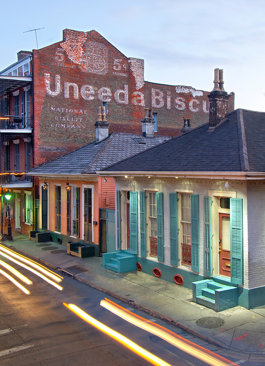 Streaking car lights at dusk on Dumaine Street in the French Quarter of New Orleans. The street and neighborhood contain many examples of the unique architecture found here as seen in the wood shutters and the   Uneeda Biscuit sign.