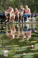 Group portrait of teenage girls and boys (16-17 years) sitting by lake smiling