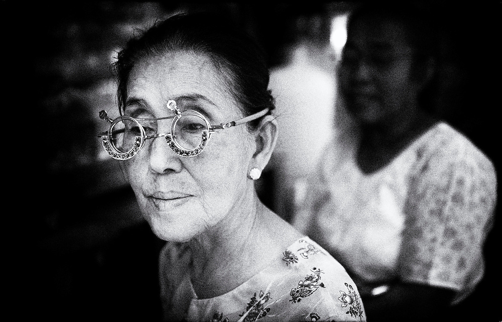 A woman has her eyes tested for new glasses at a street vendors clinic - Yangon (Rangoon) Myanmar (Burma) January 2012