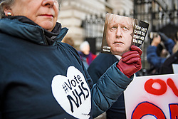 © Licensed to London News Pictures. 09/12/2019. London, UK. A woman holds up a picture of British Prime Minister Boris Johnson, as NHS workers and NHS patients hold a demonstration  outside Downing Street in Westminster calling for the NHS to be kept in public ownership. There have been claims that the NHS would be open to private ownership form foreign investment if the Conservatives win a majority in Thursday's  General Election. Photo credit: Ben Cawthra/LNP