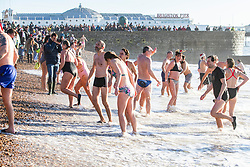 © Licensed to London News Pictures. 25/12/2019. Brighton, UK. Members of the public take part in the Brighton and Hove Christmas Day swim. Hundreds of people dress up to take a dip in the cold water. Photo credit: Hugo Michiels/LNP