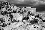 Hard tuff boulders scattered on eroded surface of softer tuff on East Mesa in the Pajarito Plateau, with storm, © 1983 David A. Ponton