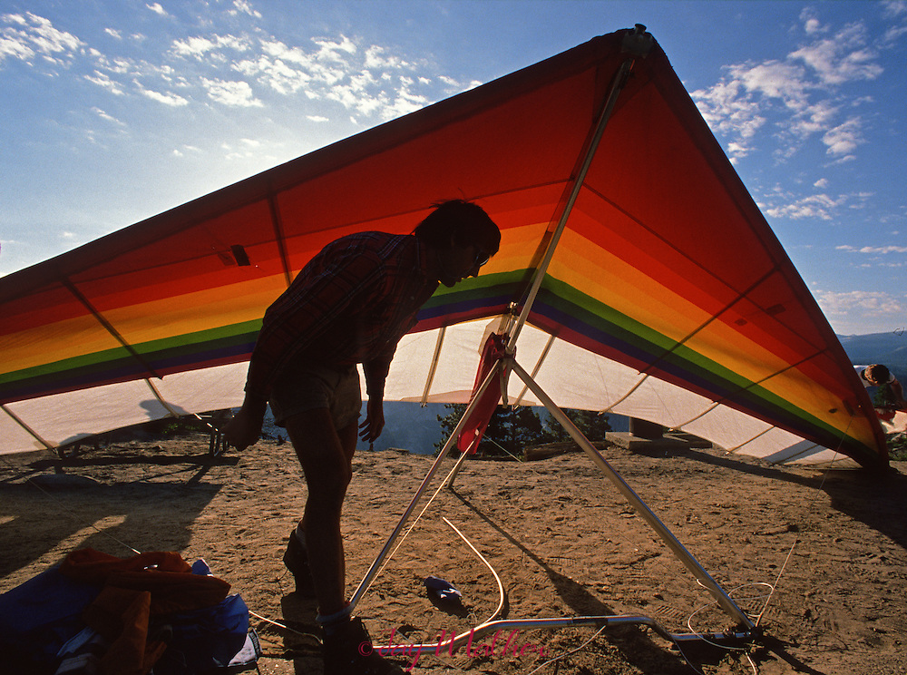 A hang glider pilot checks his kite carefully before launching off Glacier Point. The sport of hang gliding in the park is allowed and is regulated and monitored by rangers.  July 1989.