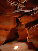 The sun casts a spot on the sand floor of the water-carved sandstone of Upper Antelope Canyon, Navajo land, Arizona.