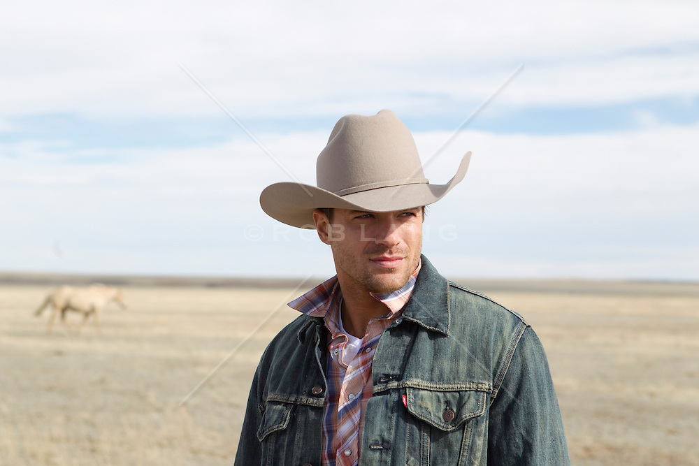 portrait of a handsome cowboy standing alone on a ranch in New Mexico