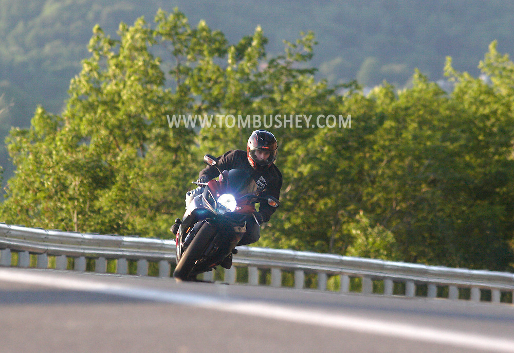 Ellenville, NY - A man rides a motorcyle around a turn on Route 52 on May 30, 2009.