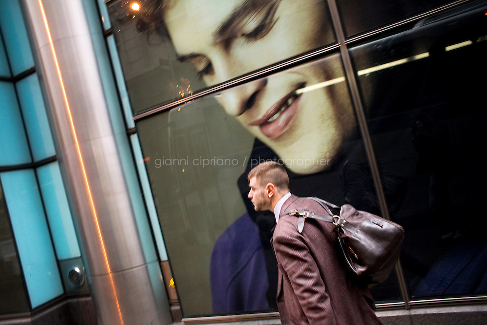 11 December, 2008. New York, NY. Daniel Alexander Osach (or Dan Alex), 24, walks his way to work on 59th street, after exiting the subway.Daniel works for Christopher Hyland, Inc., a high-end-end fabric purveyor. Daniel Osach is a gay Go-Go dancer who grew up in New Haven, CT, and moved to New York a year ago. During the day he sells fabrics. At night, he works as a Go-Go dancer in gay and women clubs around New York City. &quot;My life is work, gym, dance and sleep&quot;, Daniela says. Dan has a bachelor in English and majored in Poetry and Economics. After graduation in 2006 he worked as a store manager in a mall for 4 months in Connecticut. Tired and depressed of his job, he went to Florida to relax and then came to New York a year ago. He usually dances at &quot;The Cock&quot;, a  East Village gay bar. &quot;The Cock is not an institution. It's a landmark&quot; Daniel says. Daniel aspires to become maybe a teacher or to work for a travel magazine. &quot;What I would really love to do is to live my life laying down at the beach and reading poetry&quot;<br /> <br /> &copy;2008 Gianni Cipriano for The New York Times<br /> cell. +1 646 465 2168 (USA)<br /> cell. +1 328 567 7923 (Italy)<br /> gianni@giannicipriano.com<br /> www.giannicipriano.com