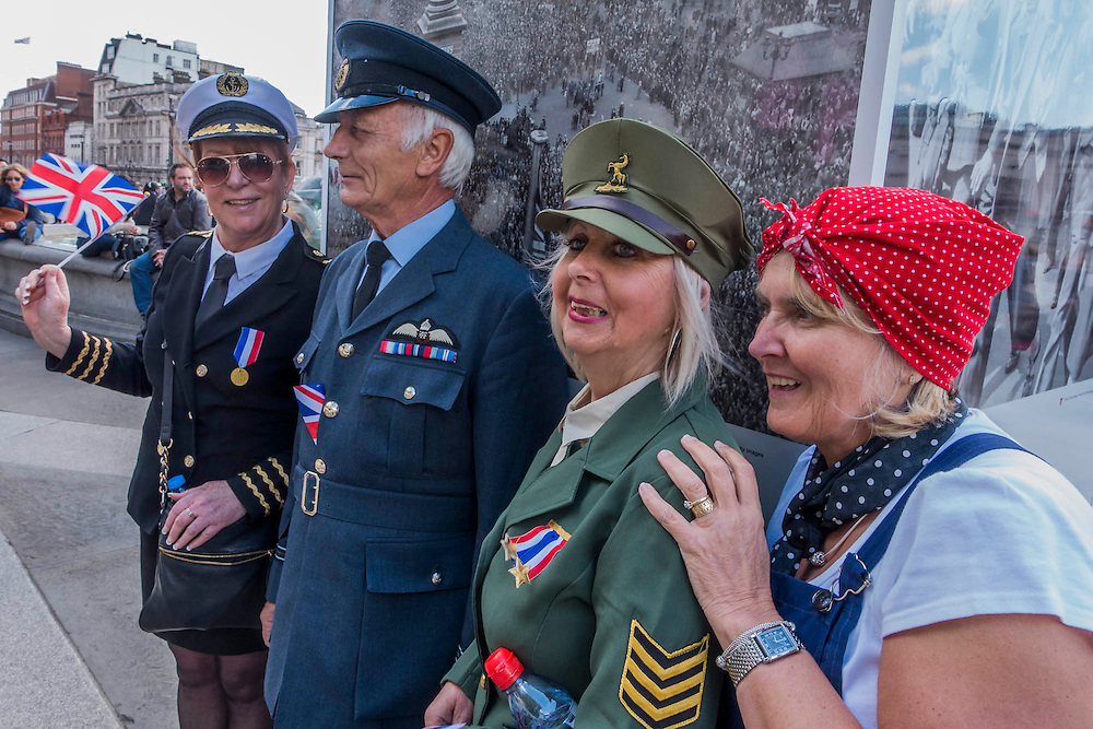 People in home made 'period' outfits pose in front of the photos of the original VE Day in Trafalgar Square. VE Day 70 commemorations - Three days of events in London and across the UK marking historic anniversary of end of the Second World War in Europe. Trafalgar Square, scene of jubilant celebrations marking the end of the Second World War in Europe on 8 May 1945, plays a central part in a host of national events, which include a Service of Remembrance at the Cenotaph, a concert in Horse Guards Parade, a Service of Thanksgiving at Westminster Abbey, a parade of Service personnel and veterans and a flypast.