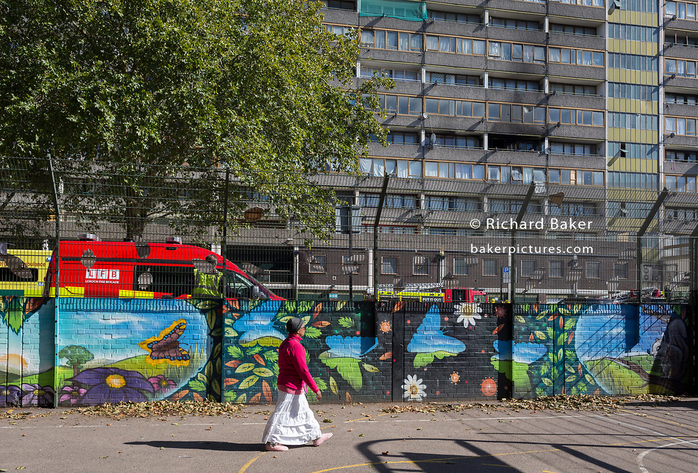 A local estate resident walks past smoke damage aftermath on the exterior of a flat fire in one of the two Wendover blocks in Alsace Road on the Aylesbury Estate, Southwark SE17, on 24th September 2018, in London, England. Part of a split level flat on the fourth and fifth floor of the 15-storey block was damaged. One woman and two children left the property before the Brigade arrived. They were treated at the scene for smoke inhalation by London Ambulance Service crews and taken too hospital. Another man was also treated at the scene for smoke inhalation.