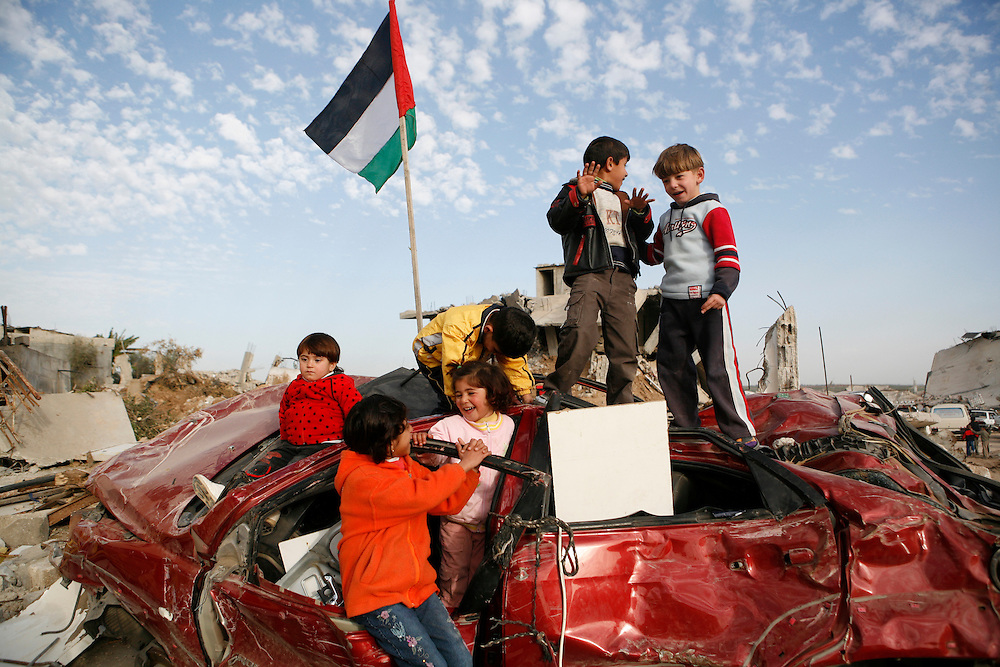 Young children play atop a destroyed car in Jabaliya, Gaza Strip.