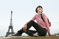 France Paris Young woman sitting on balcony in front of Eiffel Tower