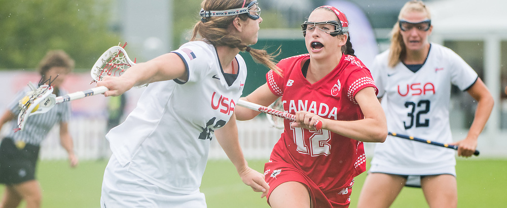 Canada's Megan Kinna(12) is caught between USA's Kayla Treanor(12) and Allyson Carey(32) at the 2017 FIL Rathbones Women's Lacrosse World Cup at Surrey Sports Park, Guilford, Surrey, UK, 15th July 2017