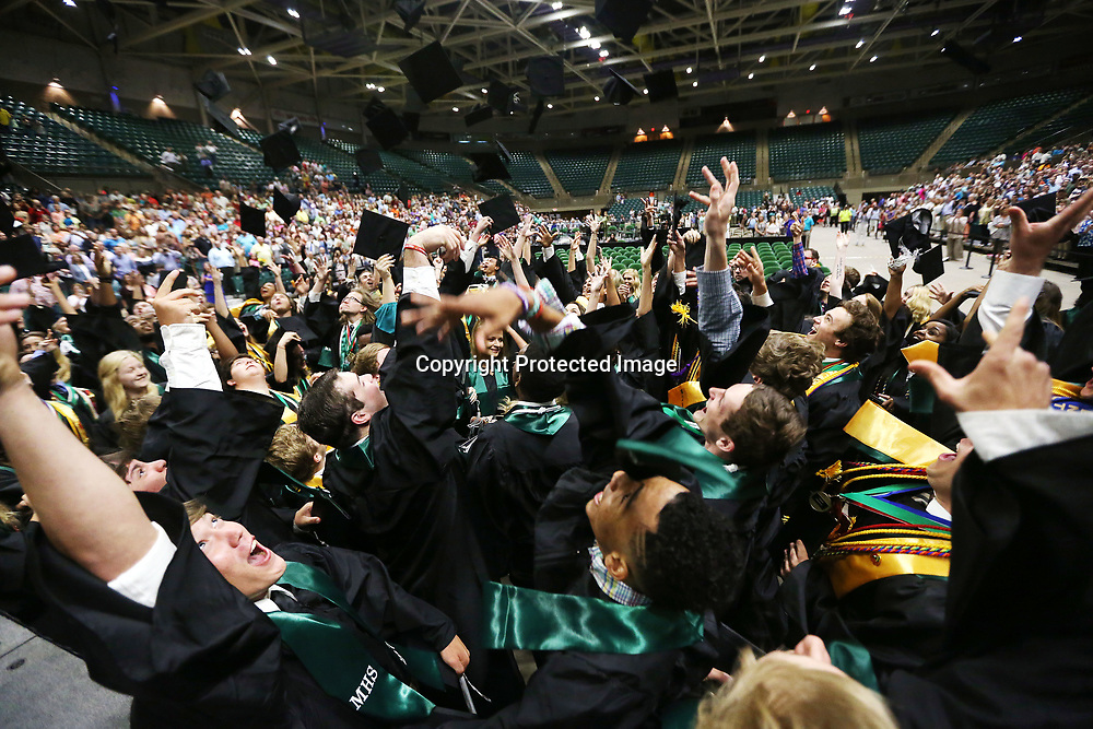 Mooreville High School graduates throw their hats in the air after Mooreville's graduation ceremony Saturday afternoon at the BancorpSouth Arena.
