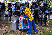 A man sells ice lollies to riot police during a student protest at the UNAH universtity in Tegucigalpa. The students are protesting the corrupt administration of the university, which discriminates against students who are opposition supporters. The protests were ongoing and the university was about to suspend another semester of classes. 10th August 2017.