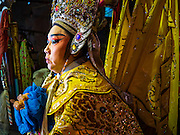 17 FEBRUARY 2016 - BANGKOK, THAILAND:   A performer relaxes backstage before a Chinese opera performance in Bangkok. She's a member of a small troupe that travels from Chinese shrine to Chinese shrine performing for a few nights before going to another shrine. They spend about half the year touring in Thailand and the other half of the year touring in Malaysia. Members of the troupe are paid about 5,000 Thai Baht per month (about $140 US). Chinese opera was once very popular in Thailand, where it is called Ngiew. It is usually performed in the Teochew language. Millions of Chinese emigrated to Thailand (then Siam) in the 18th and 19th centuries and brought their culture with them. Recently the popularity of ngiew has faded as people turn to performances of opera on DVD or movies. There are still as many 30 Chinese opera troupes left in Bangkok and its environs. They are especially busy during Chinese New Year and Chinese holiday when they travel from Chinese temple to Chinese temple performing on stages they put up in streets near the temple, sometimes sleeping on hammocks they sling under their stage. Most of the Chinese operas from Bangkok travel to Malaysia for Ghost Month, leaving just a few to perform in Bangkok.   PHOTO BY JACK KURTZ