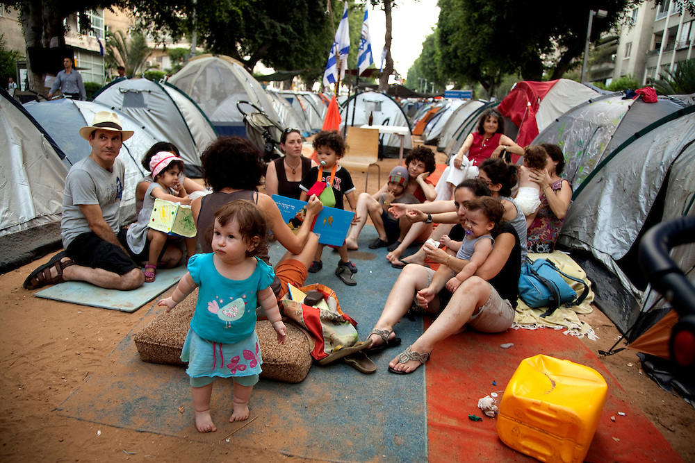 An Israeli woman improvising activities for the protestors' children which are now living in a &quot;tent city&quot; as a protest over the rising cost of living in Israel. Tel-Aviv, July 31, 2011. <br /> <br /> Two weeks after the protest over housing distress arisen in Israel, demonstrations are sweeping the country. More than 150,000 people took part in protests nationwide calling for socioeconomic changes, demanding &quot;social justice&quot;. Hundreds of people placed tents in central locations of major cities as their protest encampments (&quot;tent cities&quot;). What only started as a protest over expensive housing, rapidly accelerated to be the Israeli summer of discontent.