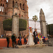 "Musicians, a ""beer"" burro and two giant papier-mâché puppets, known as mojigangas, await a soon-to-be married couple at the Parroquia in San Miguel de Allende, Mexico for an ensuing procession through the neighborhood. These looming puppets are farcical exaggerations of humanity, a tradition that can be traced to Spain."