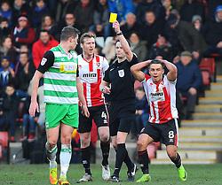 Referee Darren England shows a yellow card to Alex Lacey of Yeovil Town- Mandatory by-line: Nizaam Jones/JMP- 18/02/2017 - FOOTBALL - LCI Rail Stadium - Cheltenham, England - Cheltenham Town v Yeovil Town - Sky Bet League Two
