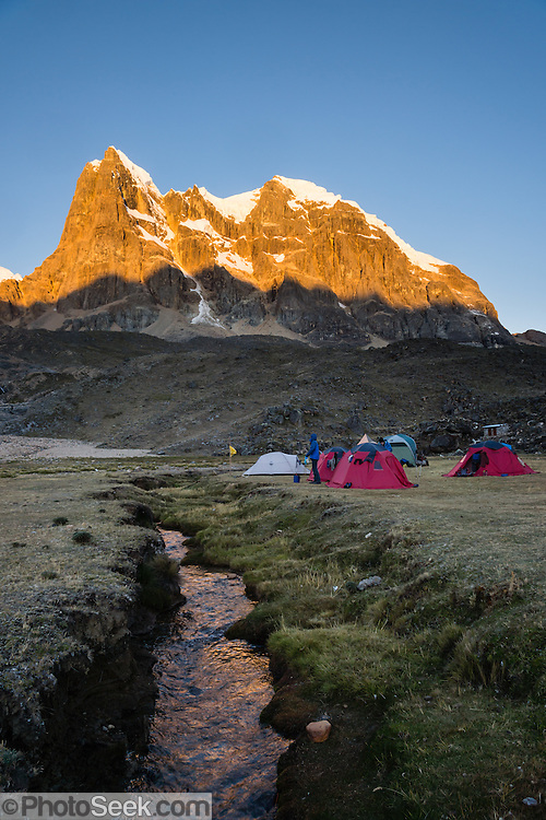 Trekkers camp at Yanapampa (4500 m) in red tents in Cuyoc Valley below Nevado Cuyoc (Puscanturpa Sur, 5550 meters). Day 5 of 9 days trekking around the Cordillera Huayhuash in the Andes Mountains, Peru, South America.