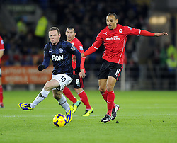Man Utd Forward Wayne Rooney (ENG) battles for the ball with Cardiff City Forward, Peter Odemwingie (NGA) - Photo mandatory by-line: Joseph Meredith/JMP - Tel: Mobile: 07966 386802 - 24/11/2013 - SPORT - FOOTBALL - Cardiff City Stadium - Cardiff City v Manchester United - Barclays Premier League.