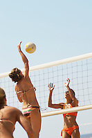 Beach volleyball player jumping to spike volleyball over net opponent defending