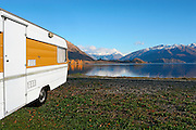 classic caravan sits beside stunning lake wanaka, with distant views of golden trees and treble cone beyond, wanaka, new zealand