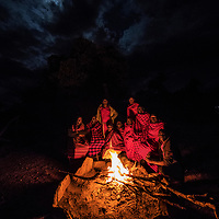 The warmth of the camp fire brings Maasai together to share stories and experiences, Masai Mara, Kenya, 2016