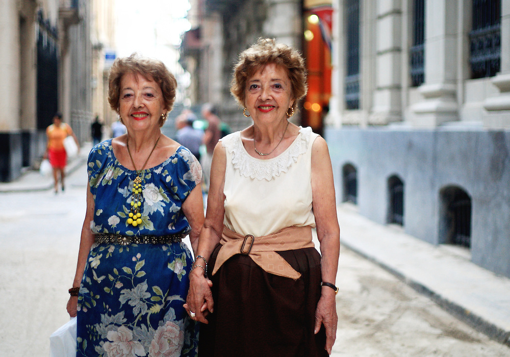 Twin sisters pose for a photo on the streets of Old Havana, Cuba.<br />