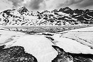 Der Aufschmelzende Lago Bianco auf dem Bernina Pass am Fuss des Piz Cambrena an einem gewittrigen Frühlingsabend im Juni