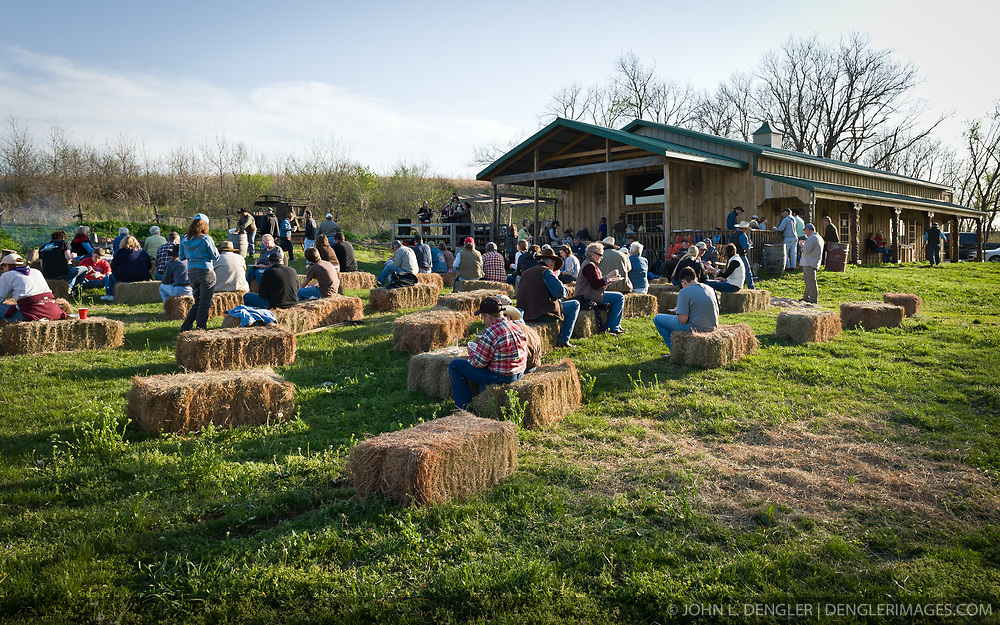 "Participants in ""Flames in the Fint Hills"" enjoy music and desert after participating in a daylight controlled burning of  prairie at the Flying W Ranch near Clements, Kansas. This agritourism event allows ranch guests to take part in lighting the prescribed burns. Prairie grasses in the Kansas Flint Hills are intentionally burned by land mangers and cattle ranchers in the spring to prepare the land for cattle grazing and help maintain a healthy tallgrass prairie ecosystem. The burning is also an effective way of controlling invasive plants and trees. The prairie grassland is burned when the soil is moist but grasses are dry. This allows the deep roots of the grasses to survive and the burned grasses on the soil surface return as nutrients to the soil. These nutrients allow for the rapid growth of new grass. After approximately two weeks of burning, new grass emerges. Less than four percent of the original 140 million acres of tallgrass prairie remains in North America. Most of the remaining tallgrass prairie is in the Flint Hills in Kansas."