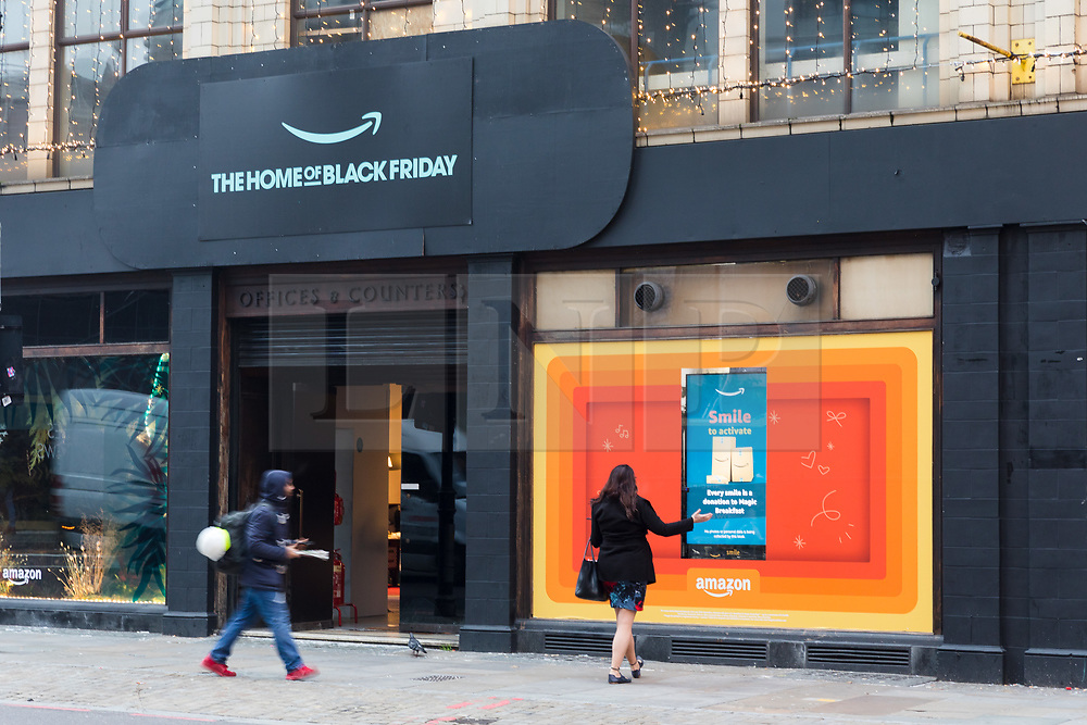 © Licensed to London News Pictures. 23/11/2018. London, UK.  People walk past the Amazon.com Black Friday pop-up shop on Shoreditch High Street in London this morning.  Photo credit: Vickie Flores/LNP