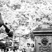 A street performer does a backflip for onlookers in Central Park.