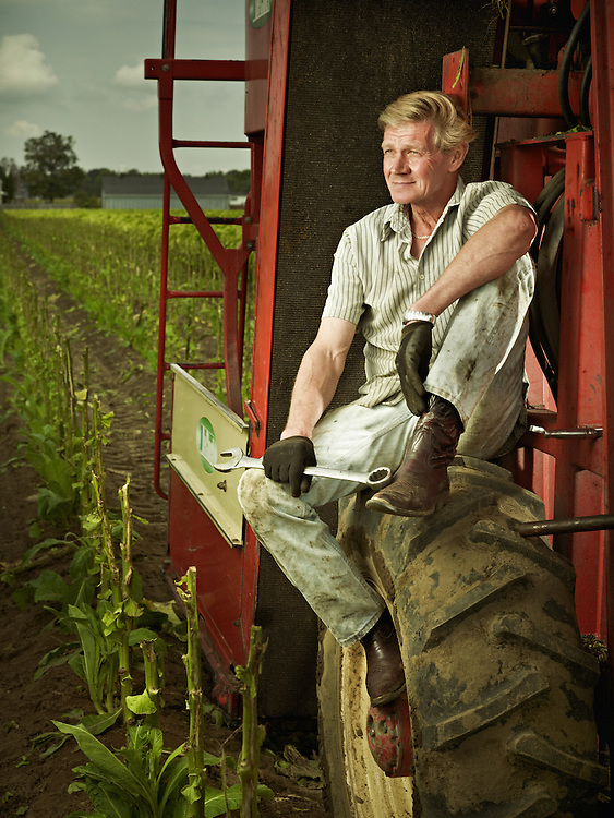 shot as a Environmental Portraiture on a PhaseOne Farmer posing on a large farm tabac harvester.