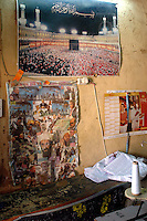 Niger, Agadez, 2007. The wall of an Agadez tailor shop displays posters of Mecca, and a composite featuring Bin Laden, Musharraf, Bush, and Qaddafi together.