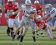 Kansas State quarterback Allan Evridge (12) rushes for a first down in the third quarter, pass Nebraska free safety Blake Tiedtke (25).  Nebraska defeated Kansas State 27-25 at Memorial Stadium in Lincoln, Nebraska, November 12, 2005.