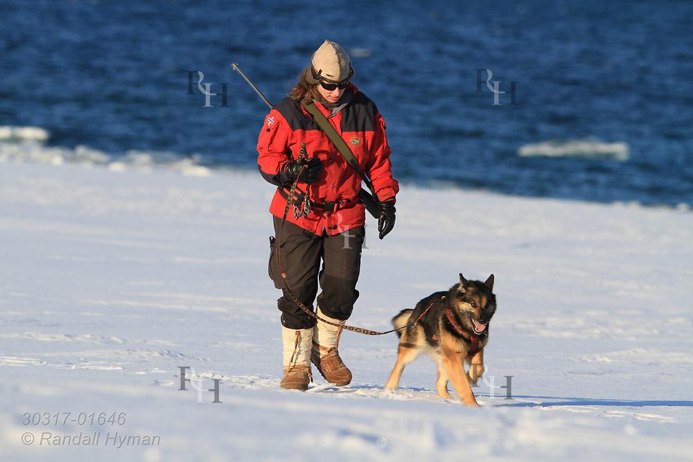 Woman walks her dog through April snows at the international science village of Ny-Alesund on Spitsbergen island in Kongsfjorden; Svalbard, Norway.