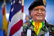 04 FEBRUARY 2011 - PHOENIX, AZ: BILL WESP, a US Army veteran of the Vietnam and first Gulf Wars, carries the American flag into the Arizona StandDown in Phoenix Friday. The Arizona StandDown is an annual three day event that brings together the Valley's homeless and at-risk military veterans, connecting them with services ranging from: VA HealthCare, mental health services, clothing, meals, emergency shelter, transitional and permanent housing, ID/ drivers license's, court services and Legal Aide, showers, haircuts and myriad other services and resources.  Arizona StandDown is held annually at the Veterans Memorial Coliseum at the Arizona State Fairgrounds in Phoenix on Super Bowl weekend.    Photo by Jack Kurtz
