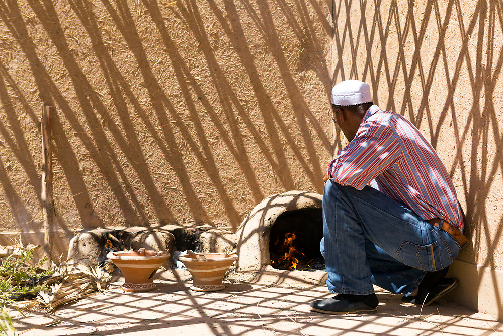 Family prepares madfouna - the Berber pizza - in a mud oven at an earthen home in Hassilabied village, Southern Morocco, 2016-04-13.<br /><br />Cooking with a mud oven remains common practice for families living in the southern Saharan areas of Morocco, where their adobe / pisé / rammed earthen homes often incorporate a well ventilated space for preparing food with this method.