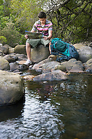 Young Hiker Reading Map by Creek