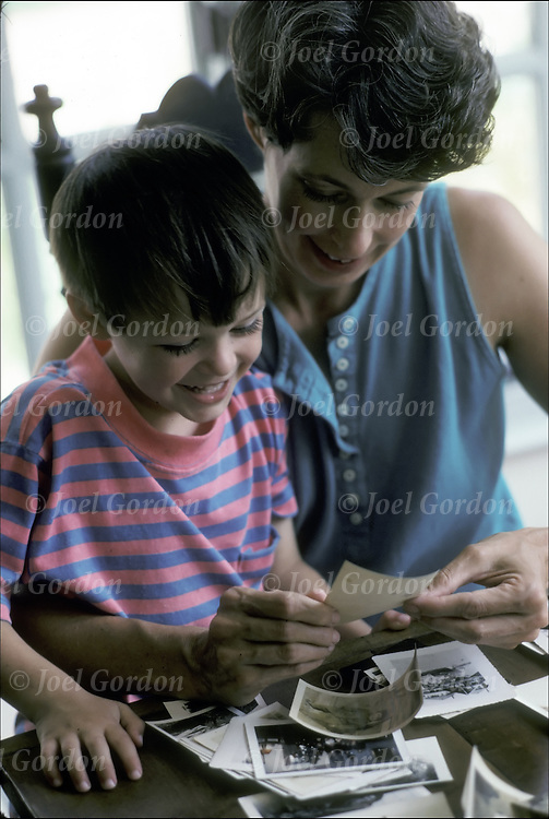 Mother and smaill son sitting at table share memories and stories with her son as they look at old photographs.
