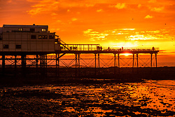 © Licensed to London News Pictures. 23/02/2019. Aberystwyth, UK. The setting sun dramatically illuminates the sky over Aberystwyth pier on Cardigan Bay in  Wales, silhouetting the people taking in the sights and some of the tens of thousands of starlings that roost for the night on the forest  of cast iron legs underneath the iconic Victorian seaside pier. Photo credit: Keith Morris/LNP
