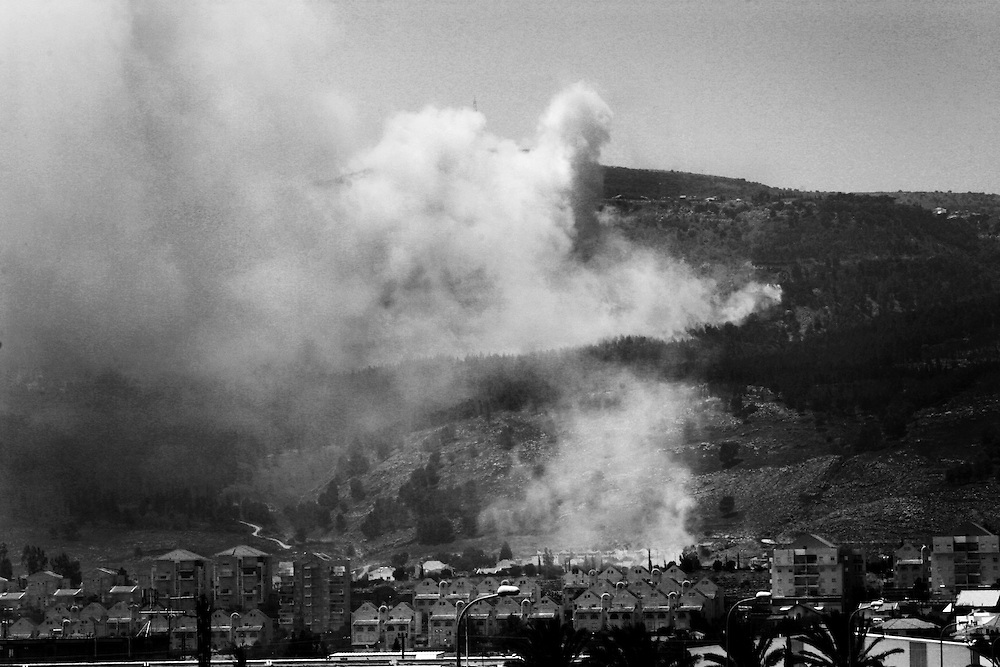 Hezbollah rockets land causing forest fires surrounding the northern Israeli town of Kiyrat Shmona. Aug 2006