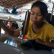 A fourteen-year old girl (foreground) is trained in her home by her elder sister (background) in the family trade of seamstressing.  Her knowledge of the skill will provide her family with an extra income to support her younger siblings.