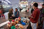 Faith D'Aluisio, one of the authors of the book What I Eat: Around the World in 80 Diets, interviews a tea seller with the help of a local translator at dawn at the Sadarghat docks on the Buriranga River dock in Dhaka, Bangladesh. (From the book What I Eat: Around the World in 80 Diets.) MODEL RELEASED.