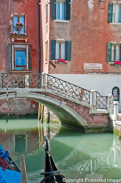 Red buildings and bridge reflecting in a green colored canal in Venice, Italy.