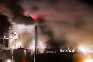Enveloped in it's own smoke and steam, an ethanol plant hums away on a cold night.