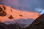 Sunset shines orange light onto the glacier under Nevado Alpamayo (19,511 ft or 5947 m) in Alpamayo Valley, Cordillera Blanca, Andes Mountains, Peru, South America. Day 6 of 10 days trekking around Alpamayo in Huascaran National Park (UNESCO World Heritage Site).