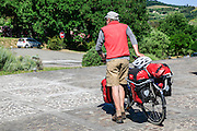 A traveller and his bicycle packet with camping equipment