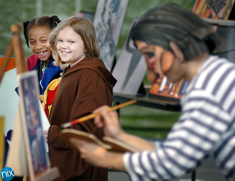 Second-grader Cariel Chambers, left, and third-grader Cierra Murkerson watch as Aaron Piepszny performs a production of the Picasso People at Golden Isles Elementary School Thursday morning.<br />
